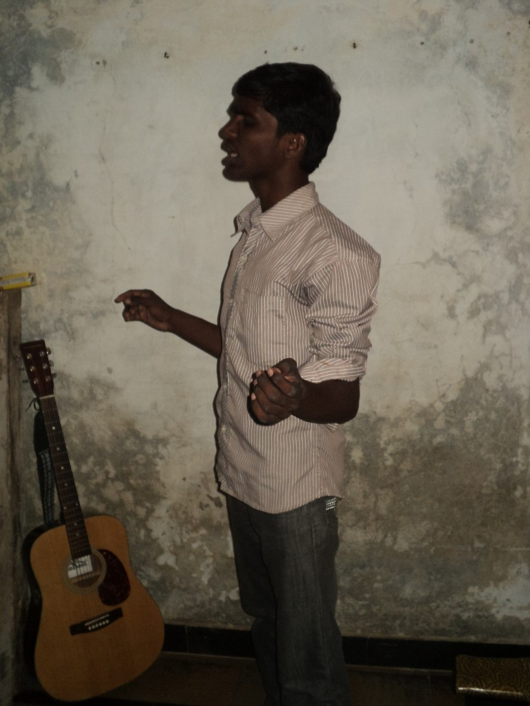 boy worshiping with wall & guitar